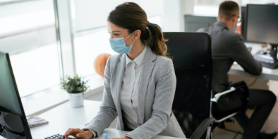 woman working at desk with PPE